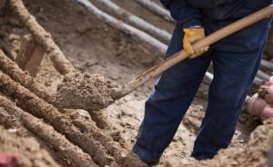 man shovelling dirt